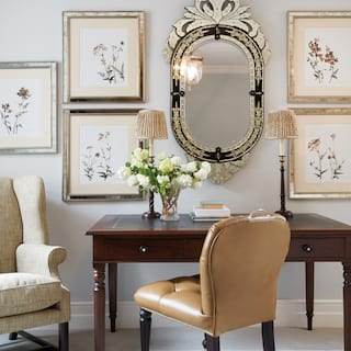 Suite lounge with writing desk and tan leather desk chair under floral paintings