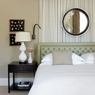 Hotel room bedside table with curved white lamp beside a pillowy king-size bed