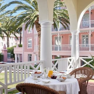 Hotel suite with white arched terrace and wicker chairs around a breakfast table