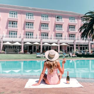 Lady in pink swim suit holding a glass of rose champagne beside an outdoor pool