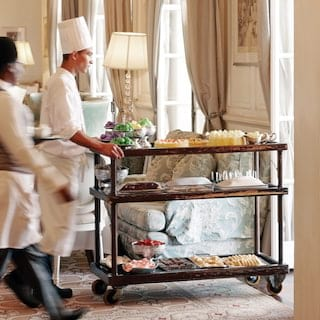 Chef in chef whites pushing an afternoon tea trolley laden with cakes and sweets