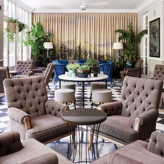 Light-filled bar with warm grey armchairs and bright blue velvet sofa