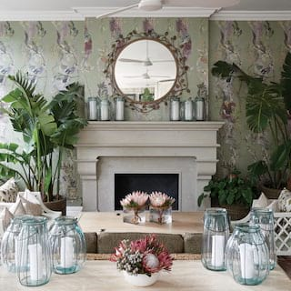 Elegant light-filled lounge with floral wallpaper, palms and candle lanterns