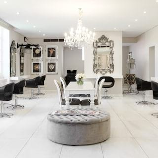 Bright marble floored hair salon lined with black leather salon chairs under a chandelier