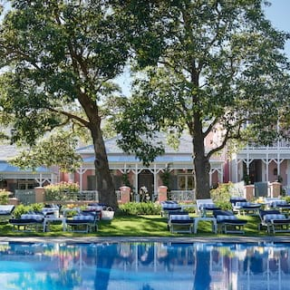 Outdoor hotel pool lined with blue sun beds reflecting trees and a pink hotel