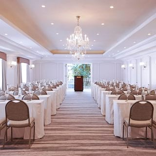 Large ballroom set with rows of banquet tables for a conference