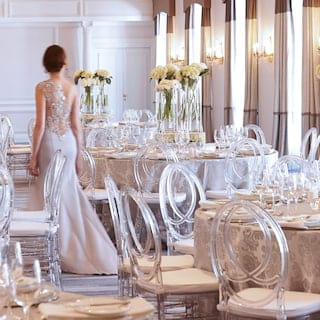 Bride in a wedding dress walking past circular wedding tables in an elegant ballroom