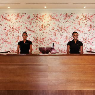 Two smiling spa therapists at a curved polished wood reception desk