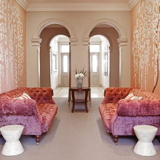 Two pink velvet sofas in a spa waiting room with pink floral wallpaper