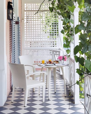 Suite patio with checkerboard tile floor and table laden with breakfast dishes