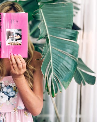 Close-up of a lady reading a pink book about tea next to a lush palm leaf
