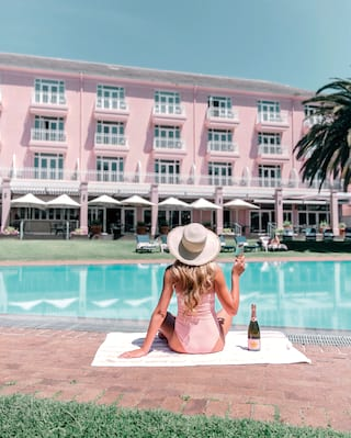 Lady in a pink swimsuit drinking champagne by a pool