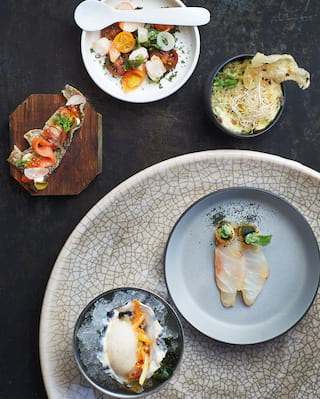 Birds-eye-view of a selection of delicious dishes served on a black slate table
