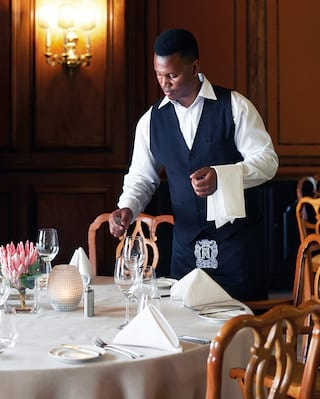 Waiter preparing a linen-coated table set with silverware and crystal glasses