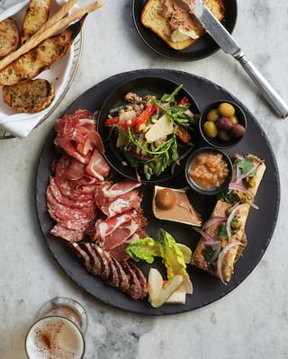 Birds-eye-view of a sharing meat platter served with a bread basket