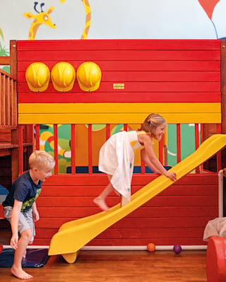 Two kids climbing a yellow slide in a brightly coloured kid's playroom