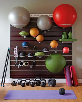 Fitness centre wall shelves with brightly coloured medicine balls and weights
