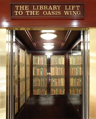 Gleaming wood-panelled Victorian lift lined with book cases