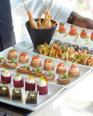 Waiter holding a white rectangular platter of various canapes