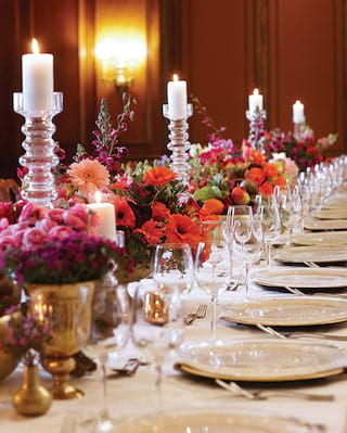 Long table set for an elegant banquet with candle and flower centrepieces