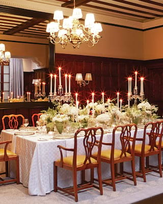 Candlelit banquet table in the centre of an elegant wood-panelled room