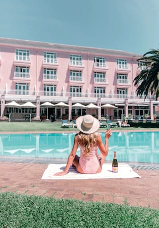 Lady in a pink swimsuit drinking pink champagne by a pool