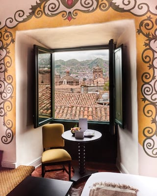 Open window in a yellow hotel room with views across the clay tiled-roofs of Cusco
