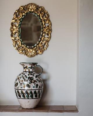 Patterned ceramic vase under a gold-gilt oval mirror