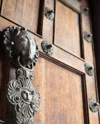 Close-up of a solid wood door and carved bronze door knocker