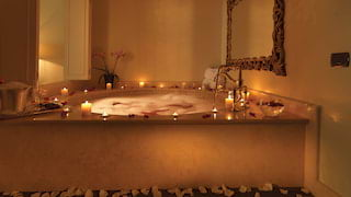 Candlelit bubble bath surrounded by petals with a champagne cooler on the side
