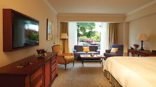 Spacious hotel room with sofa seating area, flat-screen TV and garden views