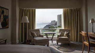 Elegant hotel room with plush armchairs and views across the Lima cityscape