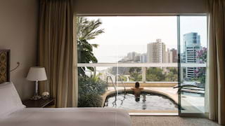 Side-view of a glass wall with a lady relaxing in a balcony plunge pool beyond