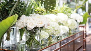 Polished wood side-table covered in vases filled with white roses and peonies