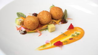 Three deep fried risotto balls garnished with avocado cubes on a circular plate