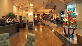 Spacious hotel lobby with polished marble floors and spiral floating stairs