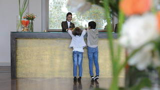 Two kids talking to a concierge at a grey and gold desk with flower arrangements