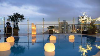 Balcony pool in evening light with floating lanterns and the cityscape beyond