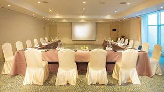 Banquet tables in a U-formation with satin pink tablecloths set for a meeting