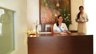 Two smiling spa therapists at a polished wooden desk