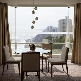 Circular glass table under pendant chandelier beside a glass wall overlooking Lima