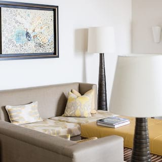 Grey and yellow patterned sofa in a stylish hotel room lounge with modern artwork