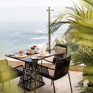 Modern ironwork table on a balcony overlooking the ocean around Lima