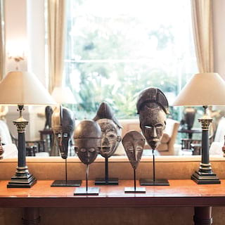 Guest lobby side-table with lamps and Peruvian mask statuettes on top