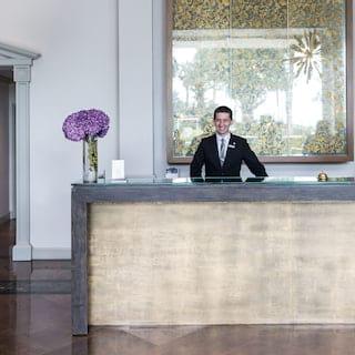Smiling concierge at a polished concrete desk with a flower arrangement