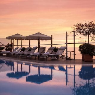 Hotel infinity pool surrounded by potted plants and sunbeds at sunset