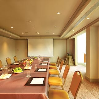 Long banquet table with orange chairs facing a flat screen in a meeting room
