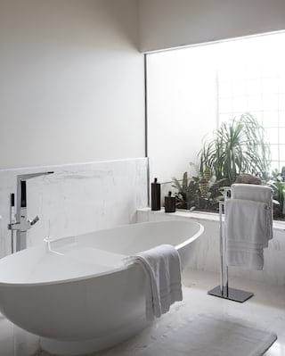 Modern standalone bathtub in a marble bathroom overlooking a balcony garden