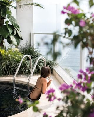 Lady in a terrace plunge pool surrounded by foliage overlooking Lima