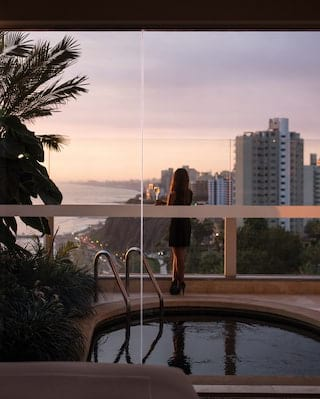 View through glass doors of sunset over Lima reflected in a balcony pool